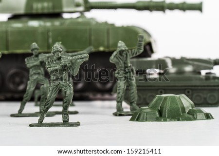 Miniature toy soldiers and tank, isolated on white background. - stock photo