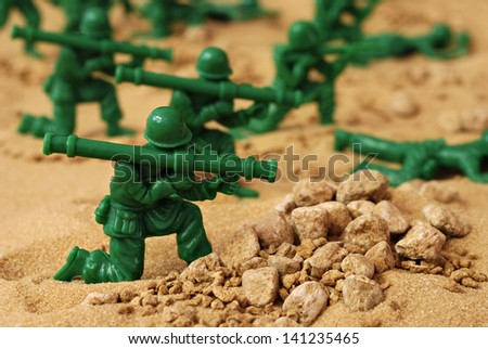 Miniature toy soldiers in desert battle scene.  Macro with shallow dof. - stock photo