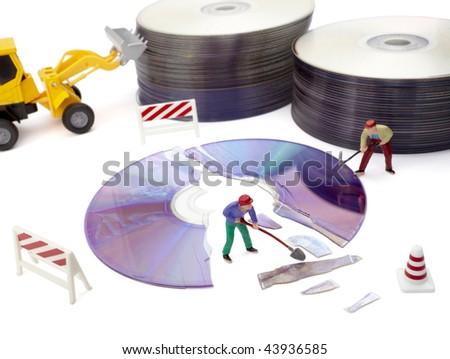 miniature toy workers repairing broken compact disk - stock photo