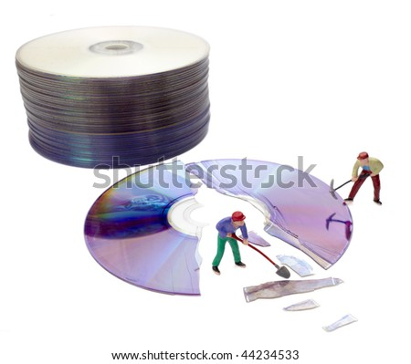 miniature toy workers repairing broken compact disk - stock photo