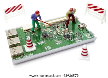 miniature toy workers repairing computer part with circuit - stock photo