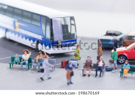 Miniature travellers at a busy bus station - stock photo