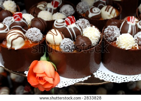 Miniature truffle-filled cakes, decorated with cherries and a rose at the wedding. - stock photo