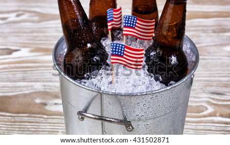Miniature USA flags in bucket of ice with bottled beer. Fourth of July holiday concept for United States of America.   - stock photo