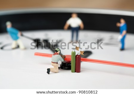 Miniature Welder At Work. A miniature figurine of a welder kneels alongside his acetylelne tanks - stock photo