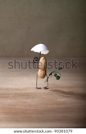 Miniature with Peanut Man taking a walk with Parasol - stock photo