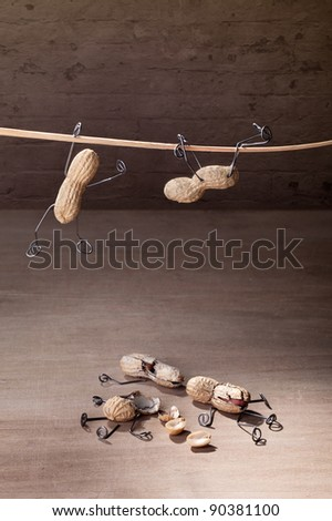 Miniature with Peanut People trying to hold their balance and grasping for a straw - stock photo