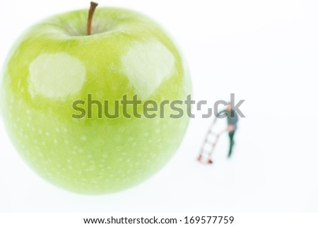Miniature worker with a sack barrow and a fresh green apple close up  - stock photo