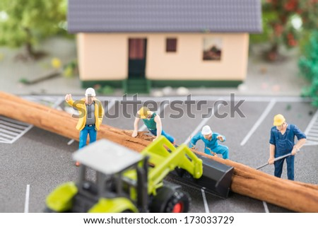 Miniature workers clearing a fallen tree after a storm top view  - stock photo