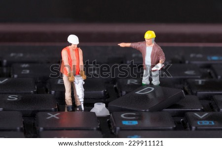 Miniature workers with drill working on a computer keyboard - stock photo