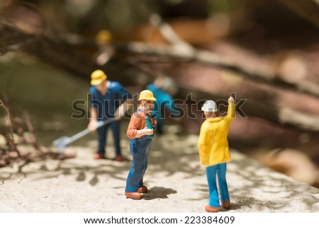 Miniature workmen clearing fallen trees on a sunny day - stock photo
