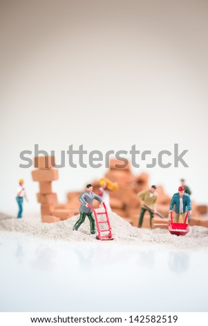 Miniature workmen doing construction work on a cloudy day with the overcast sky like background - stock photo