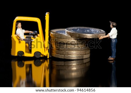 Miniature workmen with a forklift load up a pile of Euro coins for removal, macro on black with reflection - stock photo