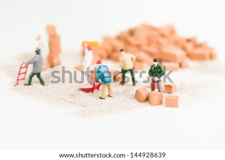 Miniature workmen working together in laying bricks close up - stock photo