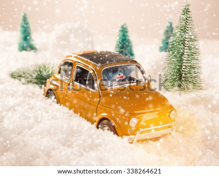 Miniature yellow car with spruce trees. Christmas theme. - stock photo