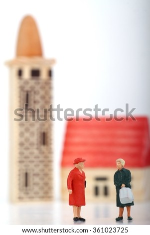 miniatures of women gossiping outside the church - stock photo