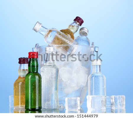 Minibar bottles in bucket with ice cubes,  on color background - stock photo