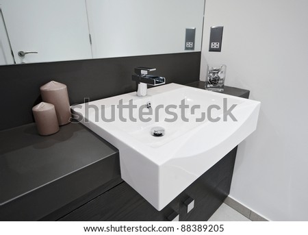 minimal style designer bathroom with rectangular hand wash and waterfall style tap - stock photo