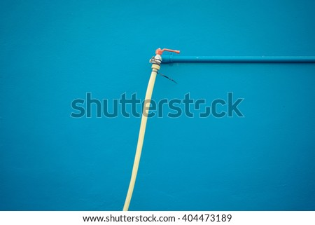 Minimalism style, Faucet metal with green water rubber tube and blue pipe on blue wall texture background. , process in vintage style - stock photo