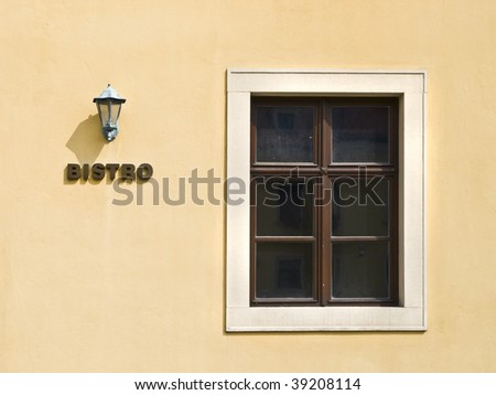 Minimalist composition of the facade of a Bistro, with a lamp and a window on the orange wall - stock photo
