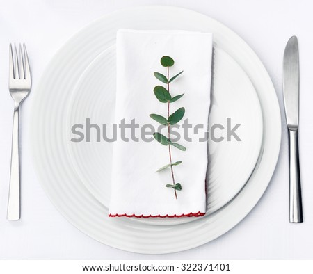 Minimalist dinner place setting, green twig on white napkin on plain crockery and silverware - stock photo