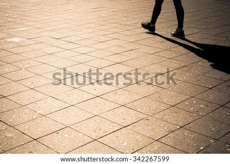 Minimalist image of person and shadow walking outdoors. - stock photo