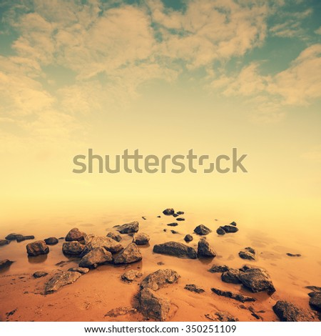 Minimalist seascape scene. Stones in water on long exposure. Image toned in retro colors - stock photo