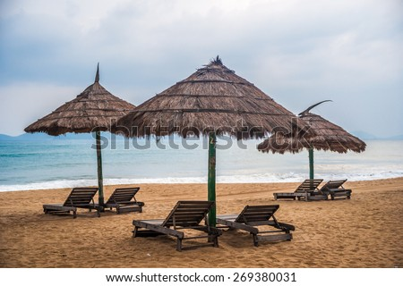 Minimalistic pgoto with three straw umbrellas on the beach with ocean and islands in the background - stock photo