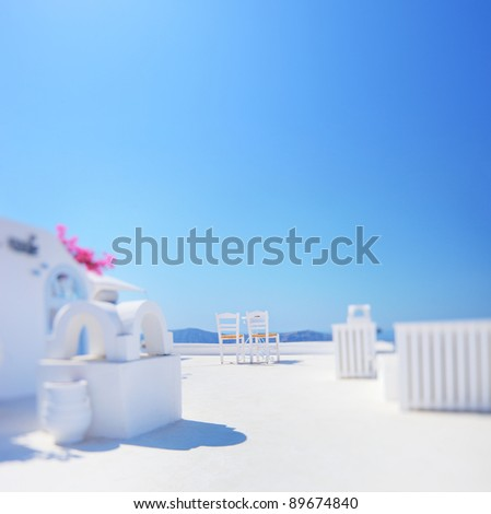 Minimalistic shot of two chairs against blue sky shot on Santorini island, Greece with tilt and shift lens and shallow DOF with the focus on the chairs - stock photo