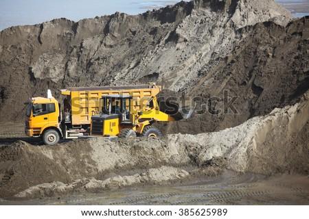 Mining dump trucks in action. - stock photo