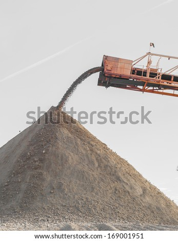 Mining industry. Barge unloading gypsum from a quarry - stock photo
