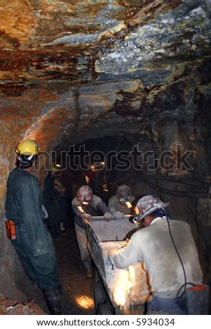 Mining - Miners pushing a tram through a silver mine.