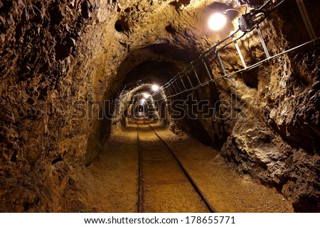 Mining tunnel with lights and rails - stock photo