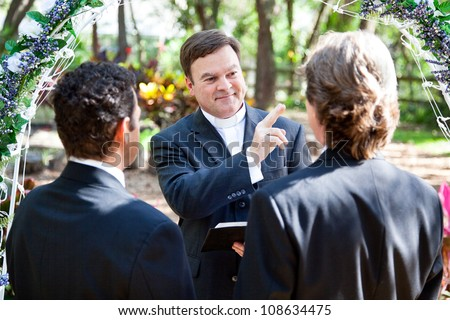 Minister blessing a gay couple while performing their wedding ceremony.