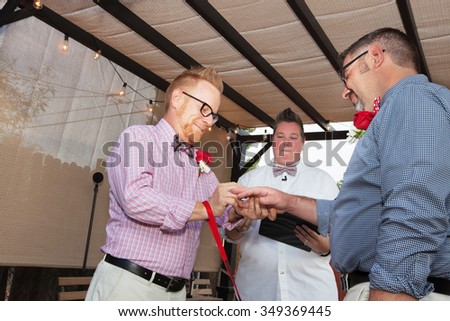 Minister with gay male couple putting on wedding rings - stock photo