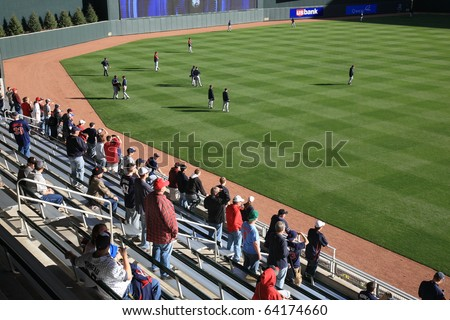 MINNEAPOLIS - APRIL 21: Twins fans watch batting practice in the sunshine at new Target Field, a ballpark that returns outdoor baseball to the city, on April 21, 2010 in Minneapolis, Minnesota. - stock photo
