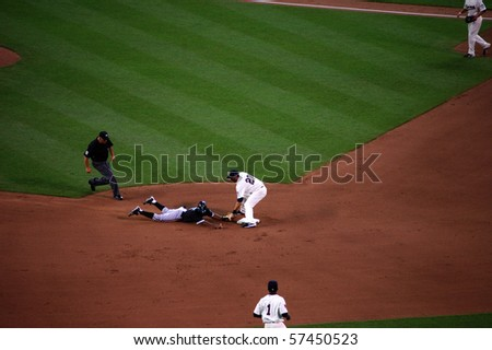 MINNEAPOLIS - JULY 17:  J.J. Hardy of the Twins tags out Juan Pierre of the White Sox, who attempted to steal second base in a game at Target Field July 17, 2010 in Minneapolis, MN. - stock photo