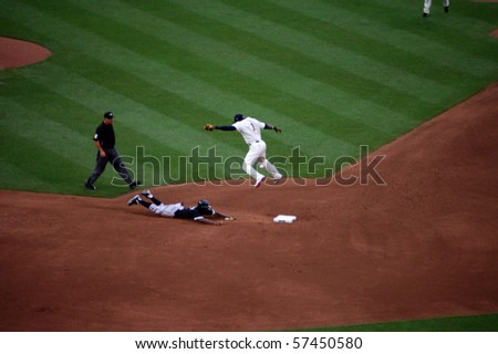 MINNEAPOLIS - JULY 17:  Juan Pierre slldes safely into second with a stolen base as A.J. Pierzynski's throw goes over Orlando Hudson's head in a game at Target Field July 17, 2010 in Minneapolis, MN - stock photo