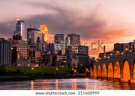 Minneapolis Minnesota Downtown and the Stone Arch Bridge at Sunset - stock photo