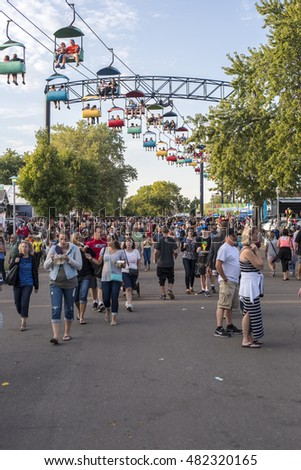 Minneapolis, Minnesota - September 3, 2016: Busy street at the Minnesota State Fair, with people on cable cars above crowd below.