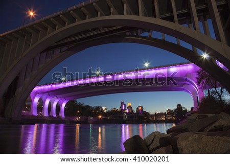 MINNEAPOLIS, MINNESOTA, USA - APRIL 22, 2016: The I-35W bridge over the Mississippi River in Minneapolis is lit with purple lights in honor of the passing of music legend Prince. - stock photo