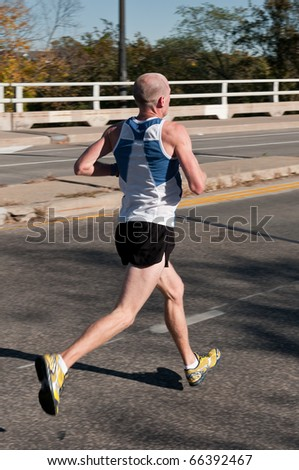 MINNEAPOLIS, MN - OCTOBER 3: Corey White runs past Mile 19 and goes on to finish 56th in the Men's Division of the 2010 Medtronic Twin Cities Marathon, October 3, 2010 in Minneapolis, MN - stock photo