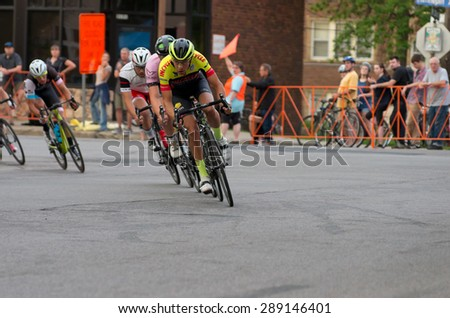 MINNEAPOLIS, MN/USA - JUNE 19, 2015: Pro cyclists lead pack at Uptown Criterium or stage four of prestigious 2015 North Star Grand Prix pro cycling event in Minneapolis.  - stock photo