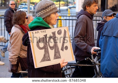 "MINNEAPOLIS - OCTOBER 29: An unidentified participant in a Occupy Minnesota protest holds up ""I'm am the 99%"" sign on October 29, 2011 in Minneapolis, MN.   Occupy protests are a worldwide movement against corporate greed. - stock photo"