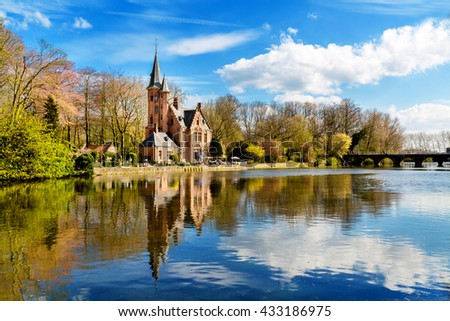 Minnewater lake panorama, reflection of gothic Flemish style building, cloudy blue sky, Bruges, Belgium - stock photo