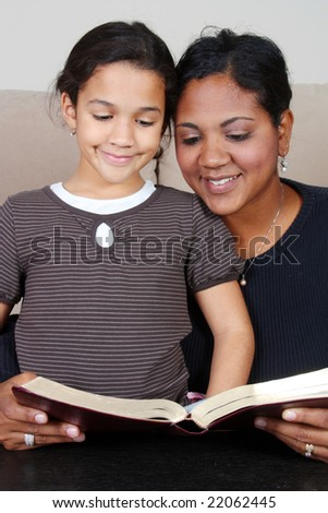 Minority woman and her daughter reading the Bible - stock photo
