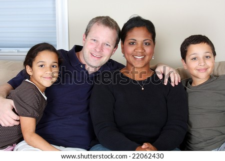 Minority woman and her family in their home - stock photo