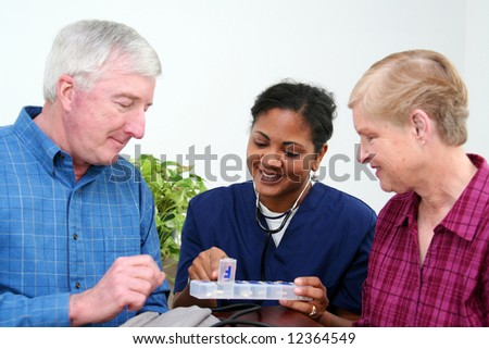 Minority woman giving healthcare to senior at home - stock photo