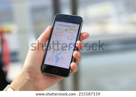 MINSK, BELARUS - AUGUST 17, 2014: Woman holding on Google Maps application on new black Apple iPhone 5S. Google Maps is most popular mapping service for mobile provided by Google.  - stock photo
