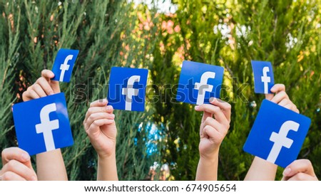 Minsk, Belarus - July, 2017: Concept. Many people. Female. Teenager. Man. Hold the logo of a popular social network Facebook.